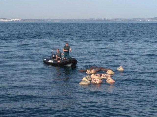 Guardia Civil rescatando fardos de hachís tirados al mar