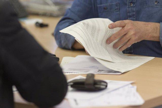 Un funcionario con papeles en una oficina de empleo.