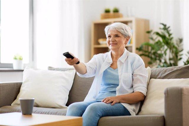 Mujer de la tercera edad viendo la televisión