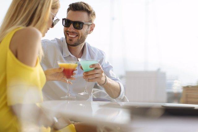 Pareja bebiendo en una terraza. Enamorados.
