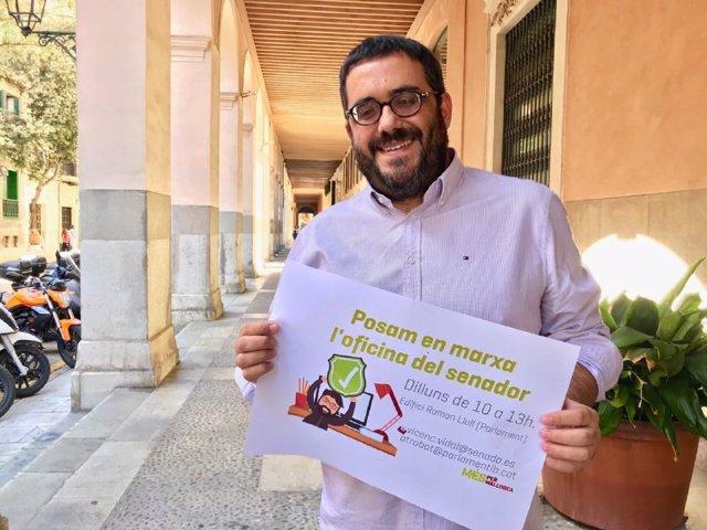 El senador de MÉS per Mallorca,  Vicenç Vidal, posa amb un cartell promocional de 'L'oficina del Senador'.