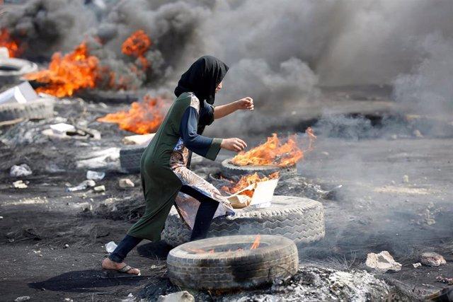 Una manifestante corre entre neumáticos ardiendo en Bagdad.
