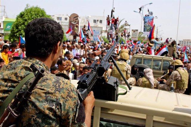 Un miembro de las fuerzas separatistas del sur rodeado de manifestantes