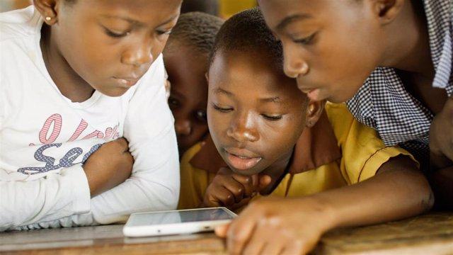 Niños ghaneses de zonas rurales utilizan una tablet como parte de un programa de Bluetown en el este del país.