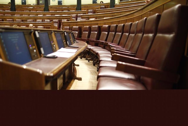 Escaños del hemiciclo del Congreso de los Diputados vacíos.