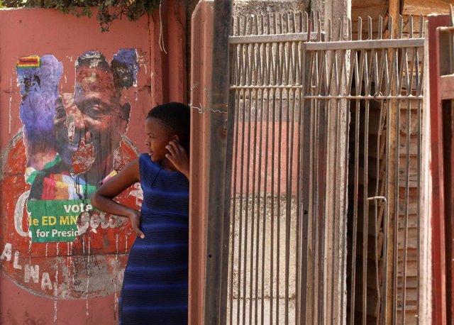 Niña junto a un cartel electoral de Emmerson Mnangagwa en Harare