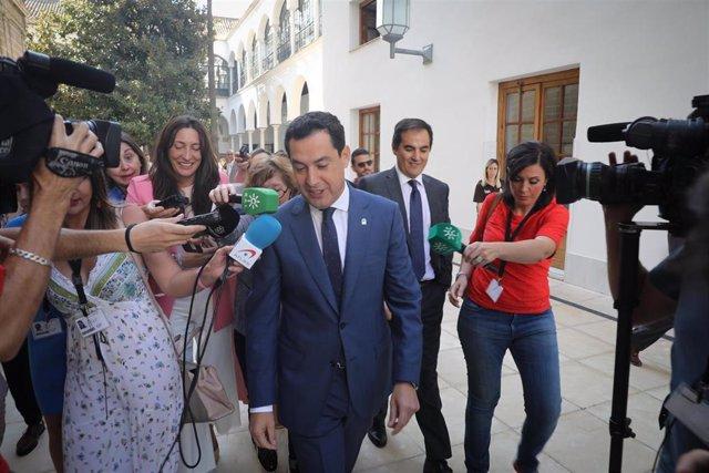 El presidente de la Junta de Andalucía, Juanma Moreno, atiende a los medios antes de entrar al Pleno del Parlamento.