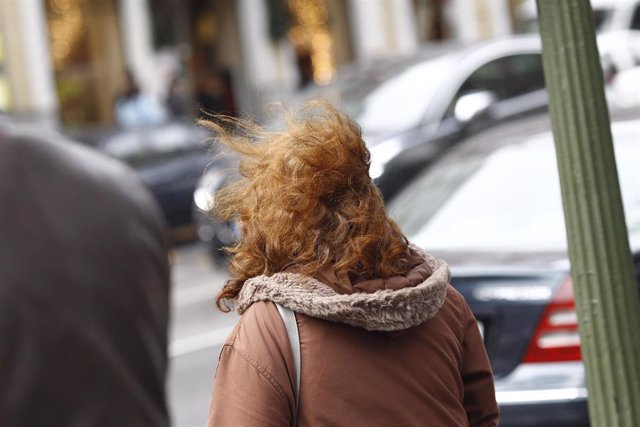 El viento despeina a un transeunte