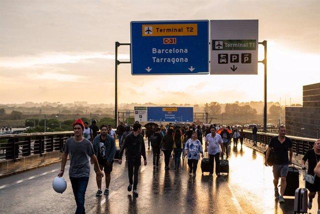 Alguns viatgers i manifestants caminen per la carretera d'accés a l'Aeroport de Barcelona-el Prat, en la jornada de concentració en protesta per la sentència del Tribunal Suprem sobre el judici del procés, Barcelona (Espanya), 14 d'octubre del 2019