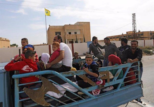 Personas sobre un camión en Tal Abyad