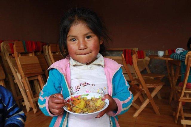 Niña con un plato en Perú