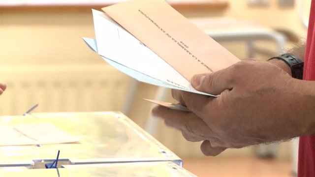 Un elector con las papeletas junto a la urna