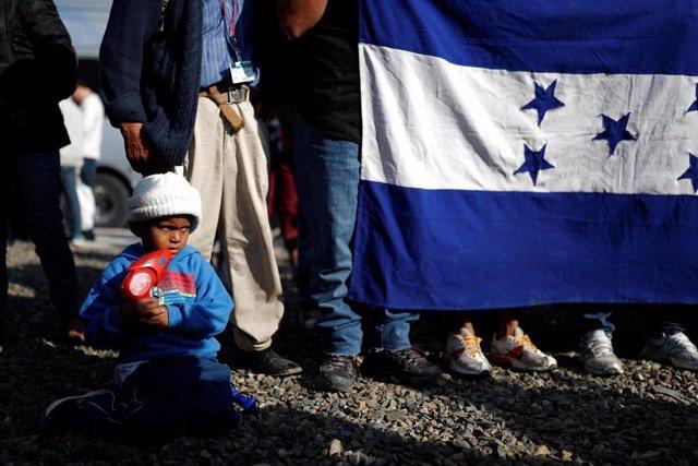 Migrantes hondureños con una bandera de su país en México