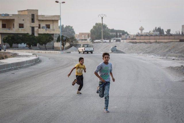 Dos niños en una calle desierta en Tel Abyad