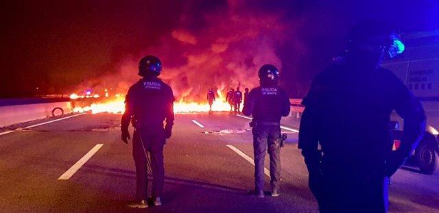 Mossos davant d'una barricada cremant a l'autovia AP7 prop de Girona per la vaga general a Catalunya.