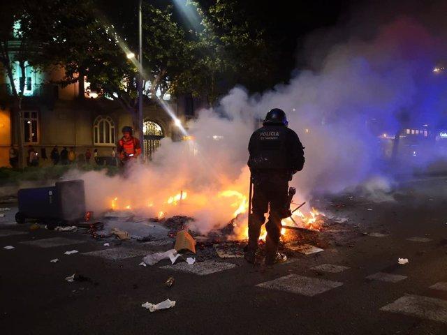 Un mosso d'Esquadra intenta apagar una foguera durant disturbis dels CDR a Barcelona contra la sentncia del processo independentista