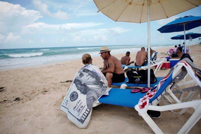 Una turista con una toalla con el símbolo de un billete de 100 dólares en una playa de Cuba