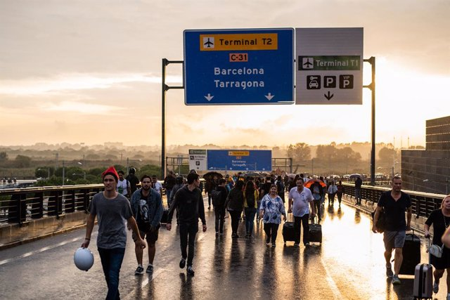 Alguns viatgers i manifestants caminen per la carretera d'accés a l'Aeroport de Barcelona-El Prat, en la jornada de concentració en protesta per la sentència del Tribunal Suprem sobre el judici del procés, a Barcelona (Espanya), a 14 d'octubre de 2019.