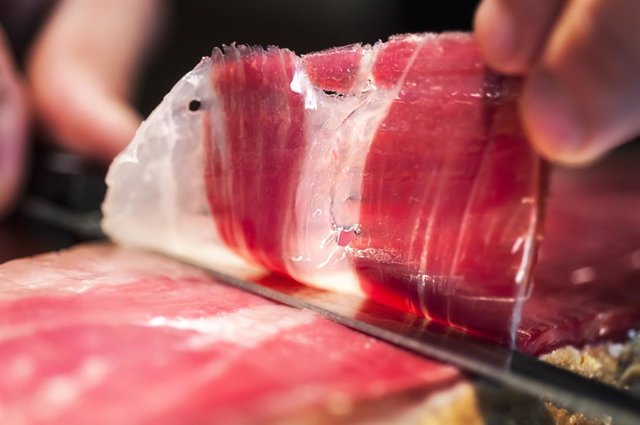 Detail of knife cutting jamon iberico