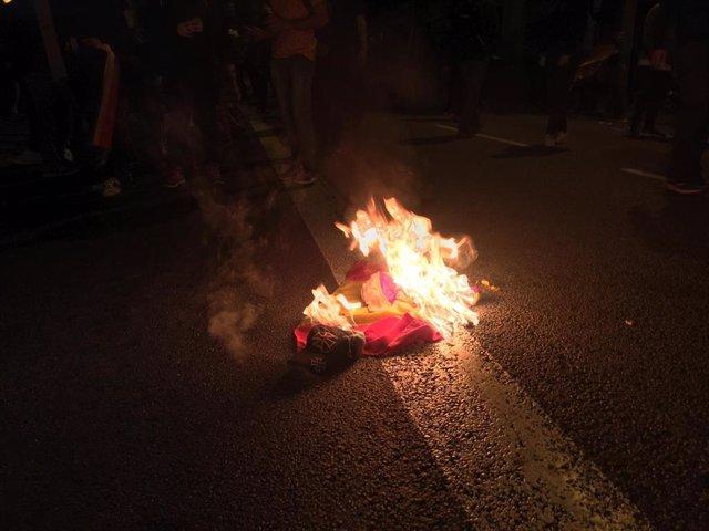 Un grup d'antifeixistes crema una bandera preconstitucional després d'agredir a un ultra en disturbis arran de la sentència contra el procés independentista