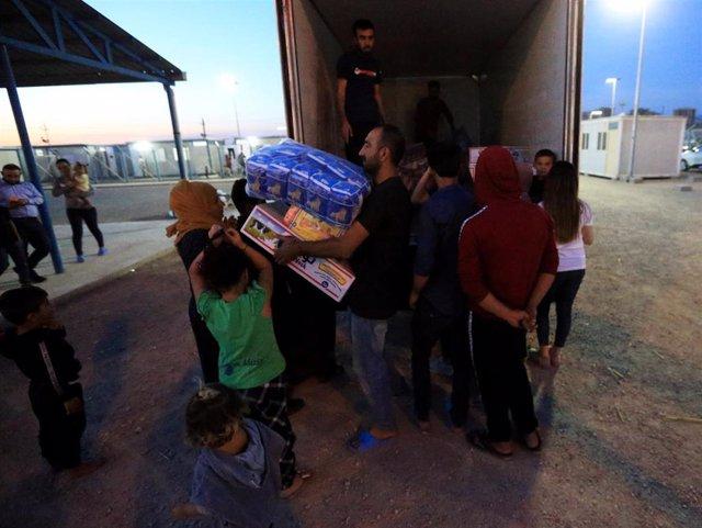 Entrega de ayuda a refugiados sirios en el campo de Domiz, a las afueras de Dohuk (Irak)