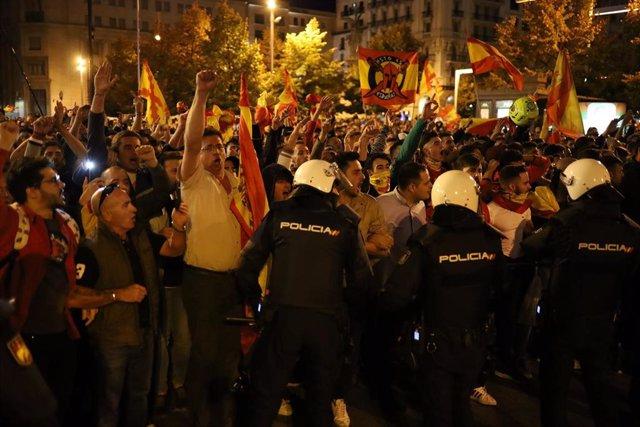 Manifestantes por la unidad de España ondean banderas españolas, mientras agentes de la Policía Nacional controlan que no haya altercados con los CDR Aragón