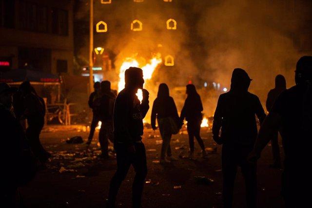 Varios manifestantes frente al fuego de una hoguera durante los disturbios en la Plaza de Urquinaona, en Barcelona a 18 de octubre de 2019.