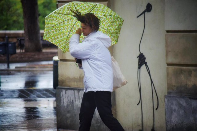 Una mujer camina por la calle sujetando su paráguas, movido por el viento, durante el temporal de gota fría que afecta a la zona de Levante, en Valencia (España) a 11 de septiembre de 2019.