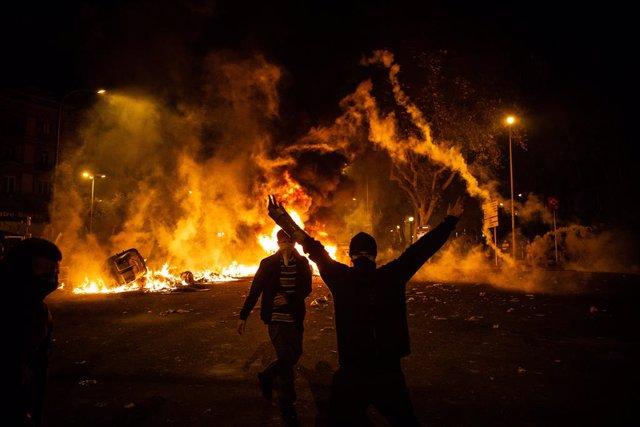 Un manifestant aixeca els braços al costat del foc d'una foguera durant els disturbis a la Plaça d'Urquinaona.