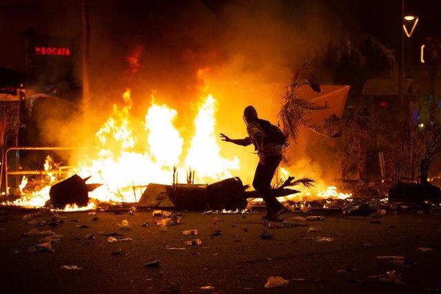 Un manifestants corre enfront del foc durant els disturbis a la Plaa d'Urquinaona, a Barcelona a 18 d'octubre de 2019.