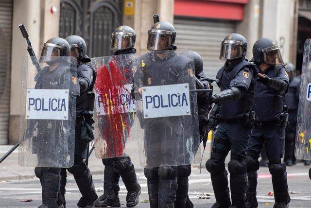 Agentes de la Policía Nacional son alcanzados por balas de pintura durante la manifestación organizada por los sindicatos Intersindical-CSC e IAC en Barcelona durante la huelga general en Catalunya en reacción a las penas por el 1-O, en Barcelona (Cataluñ