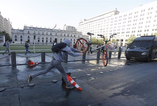 18 October 2019, Chile, Santiago: A man throws a bike during a protest against the rising costs for subway and bus tickets. Photo: Cristobal Escobar/Agencia Uno/dpa