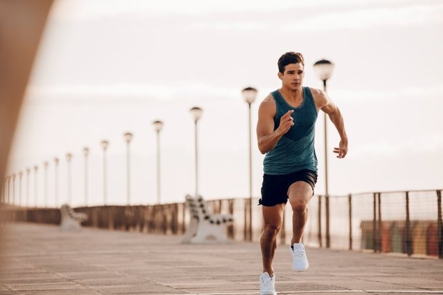 Male runner sprinting outdoors in morning