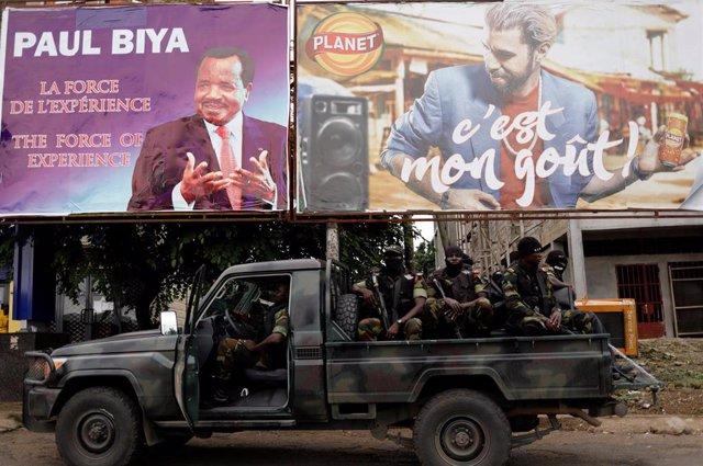 Soldados del Batallón de Intervención Rápida ante cartel electoral en Buea