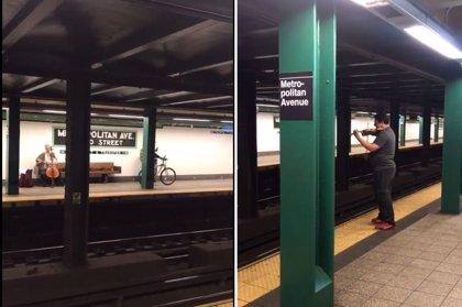 Dos músicos de la calle improvisan un concierto en andenes opuestos en el metro de Nueva York