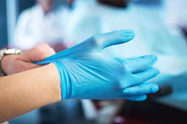 Female doctor's hands putting on blue sterilized surgical gloves.