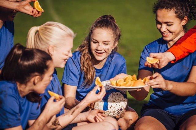 Adolescentes futbolistas femeninas tomando una naranja para reponer fuerzas.