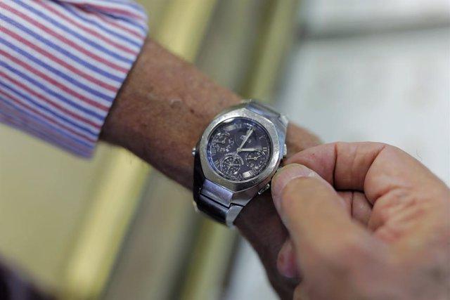 Un home mou la maneta del rellotge per canviar l'hora.