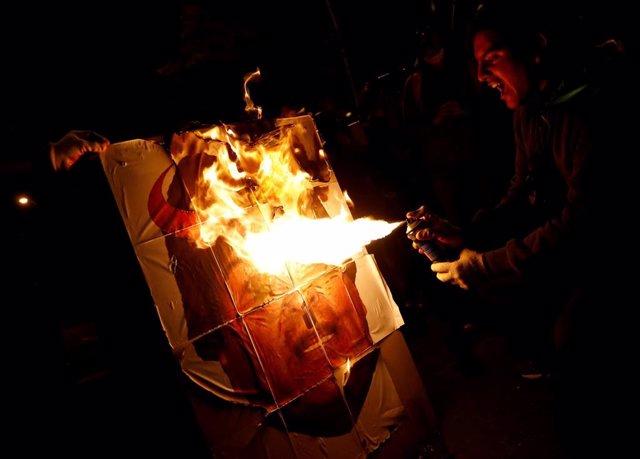 Manifestantes queman un cartel con la cara del presidente boliviano, Evo Morales