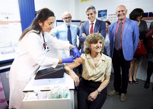 Una trabajadora del Centro de Salud del barrio de Cazoña vacuna a la  la ministra de Sanidad, Consumo y Binestar Social en funciones, María Luisa Carcedo de la gripe, tras el acto de presentación de la campaña de vacunación contra la gripe, en Santander /