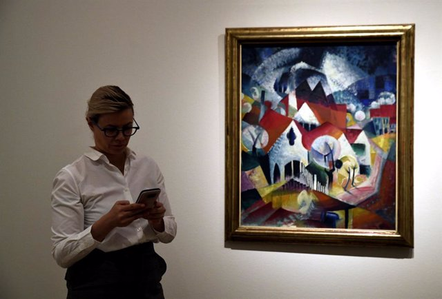 Una dona al costat de l'obra de Johannes Itten, 'Grup de cases a la primavera'  (1916) en  l'exposició 'La Bauhaus en las colecciones Thyssen' al Museu Thyssen, a Madrid (Espanya), a 28 d'octubre del 2019.