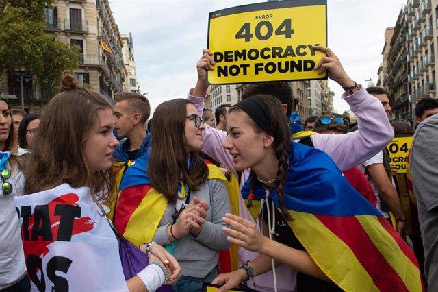 Un chico sujeta un cartel en el que se lee, `Error 404 Democrazy Not Found junto a otras chicas con la bandera de la estelada