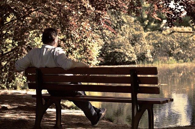 Hombre mayor sentado en un banco.