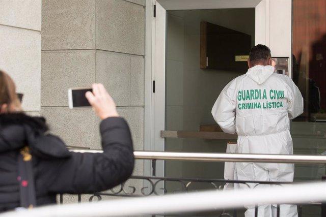 Una dona fotografia un treballador de Criminalística de la Gurdia Civil que entra a l'habitatge on un menor d'edat va assassinar presumptament la seva mare la nit de diumenge a dilluns, a Foz (Galícia).