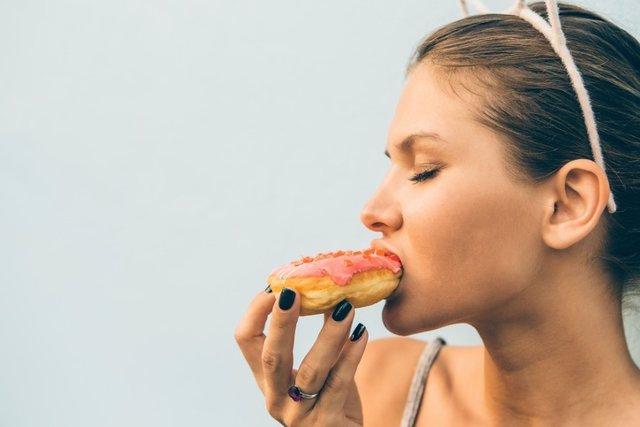 Sexy brunette lady eat sweet heart shaped donut.