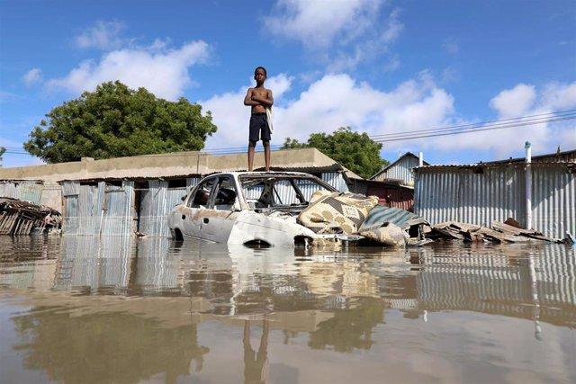 Un niño somalí parado sobre un coche destruido por las fuertes inundaciones en Mogadishu