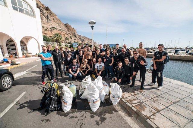 Buceadores recogen basura del fondo marino del puerto de Aguadulce en Roquetas de Mar (Almería)