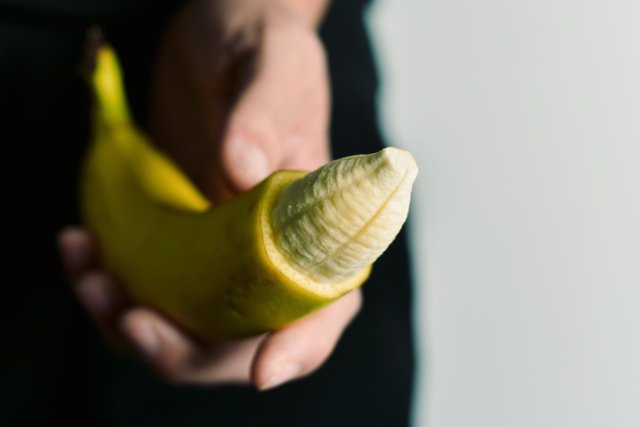 Man with banana with its tip removed