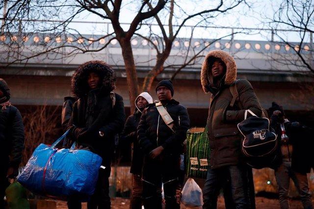 Migrantes durante un desalojo en París