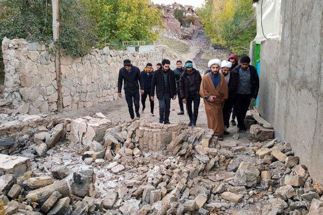 Hombres caminan sobre los destrozos materiales tras el terremoto  registrado en el noroeste de Irán